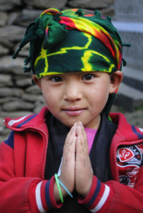 """Caption: Sangmo, a Nepalese girl, makes the classic greeting sign, namaste.  Her well-deserved nickname is """"Buta Maya"""" which means """"sweet little thing."""" Sangmo and her family came to the clinic where Ken Harvey volunteered in Nepal.  The wrap on her head, while in nontraditional colors, tells a bit of her heritage. Harvey will speak and show his photos of Nepal at the Nashua Public Library on January 7 at 7 p.m. Photo credit: Ken Harvey"""