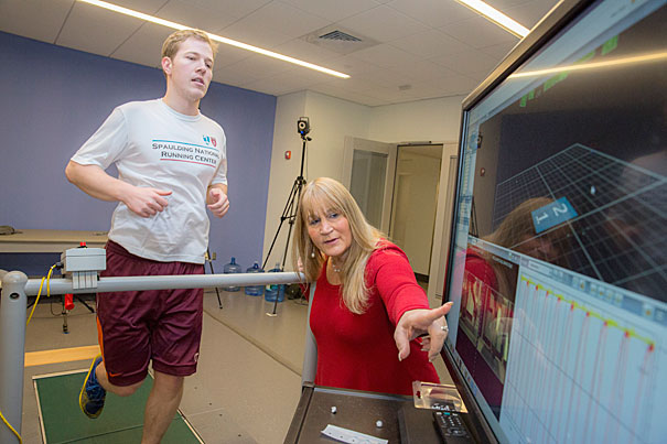 """Irene Davis, a professor of Physical Medicine and Rehabilitation at HMS and head of the National Running Center at Spaulding Rehab in Cambridge (pictured), made a study that shows runners who run """"lightly"""" have fewer injuries. On the treadmill is Laboratory Engineer at Spaulding National Running Center, Matthew Ruder. Kris Snibbe/Harvard Staff Photographer"""