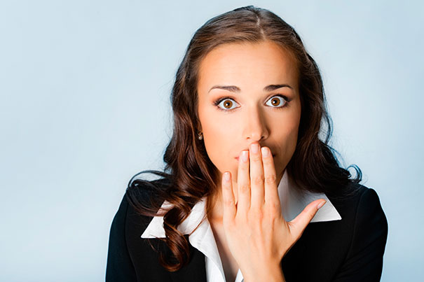Portrait of surprised excited young business woman covering with hands her mouth, over blue background Photo: (Harvard Gazette/IStock))