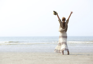Woman with raised arms at the beach celebration from behind