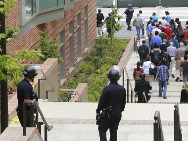Los Angeles Police officers escort people at the UCLA campus after a fatal shooting at the University of California, Los Angeles, Wednesday, June 1, 2016, in Los Angeles. Los Angeles police chief says shooting at UCLA was murder-suicide. (Photo courtesy: AP Photo/Damian Dovarganes)