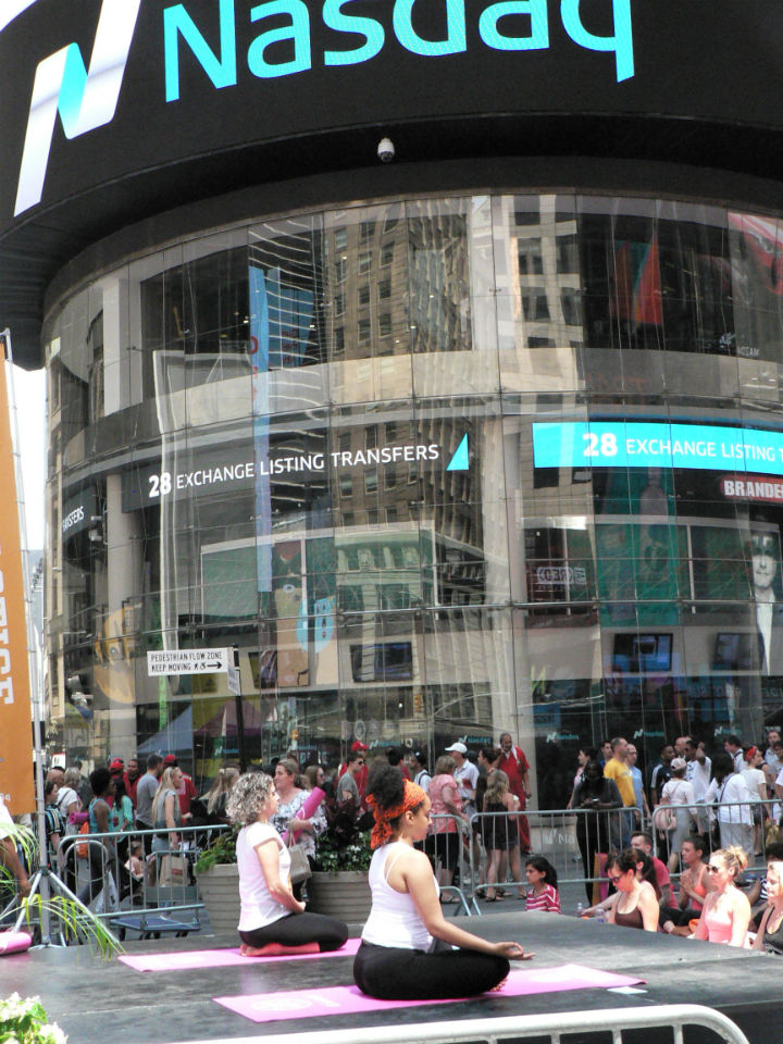 International Day of Yoga was celebrated Monday, June 20, to coincide with the Summer Solstice in New York's Times Square. A yoga session is in progress in front of the NASDAQ stock exchange building. (Credit: IANS)