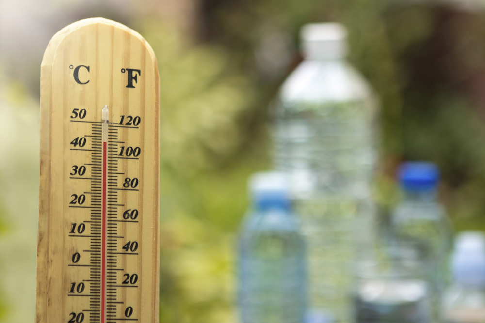 warm weather and water,  thermostat shows high temperature with water bottles in the background