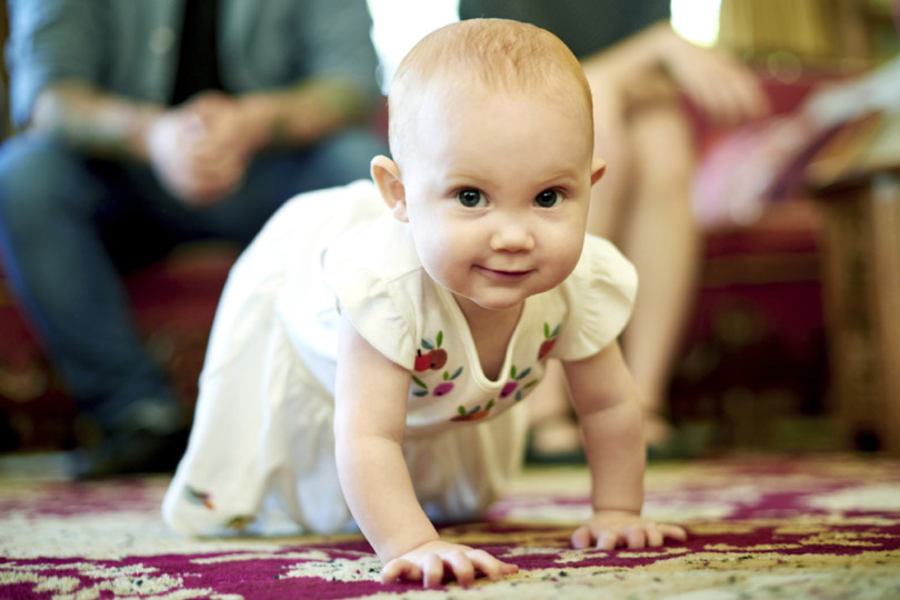 Portrait of an adorable baby girl crawling on the floor at home