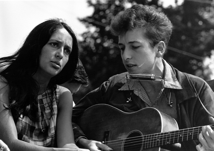 Bob Dylan with singer Joan Baez. who would also render his songs, at a priest rally in the 1960s