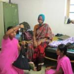 Geetha and Varalakshmi, ASHAs from Ballari, study the baby's weight